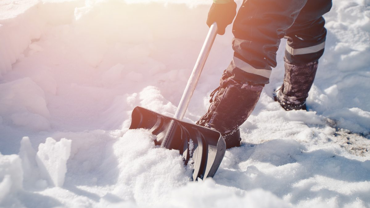 Man shoveling snow off of driveway